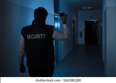 Rear View Of A Security Guard Standing In Corridor Of The Building Using Flashlight