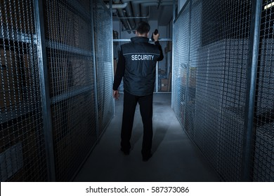 Rear View Of A Security Guard Standing In The Warehouse Holding Flashlight