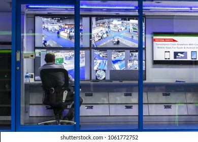Rear view of security guard watching and operating CCTV video monitoring surveillance security system at desk in office.