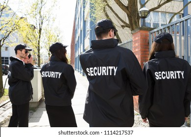 Rear View Of Security Guards In Black Uniform Standing Outside Building