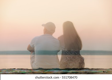 Rear view of semi-transparent man and woman in summer dress sitting on beach towel looking at sea on sunset.