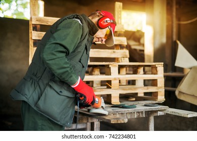 Rear view of senior carpenter burning wood with electric grinder tool in a professional uniform.