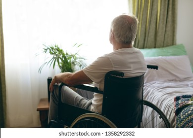 Rear view of senior Caucasian male patient looking outside the window while sitting in wheelchair in bedroom at retirement home