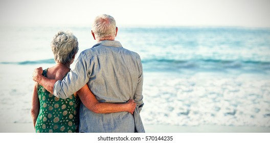 Rear view of senior couple at beach against sea