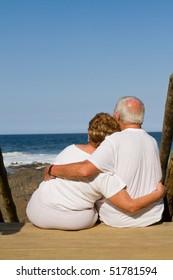 rear view of senior couple cuddling on beach