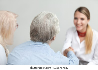 Rear view at senior couple handshaking medical worker visiting doctor, older family and financial advisor or lawyer shaking hands at meeting, happy grey-haired aged elderly clients making deal