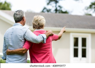 Rear view of senior couple looking at house while standing ih yard