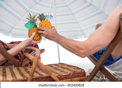 Rear view of senior couple sitting on deckchairs while toasting pineapple cocktail on the beach