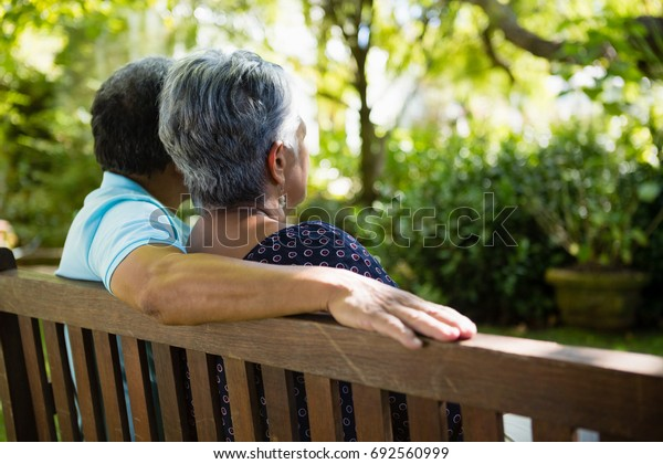 Rear view of senior couple sitting in garden on a sunny day