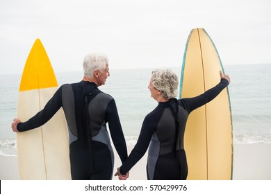 Rear view of senior couple with surfboard holding hand on the beach on a sunny day