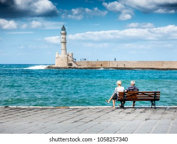 Rear view of senior couple watching old harbor from jetty, Chania, Crete, Greece