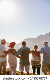 Rear View Of Senior Friends Visiting Tourist Landmark On Group Vacation Standing On Wall