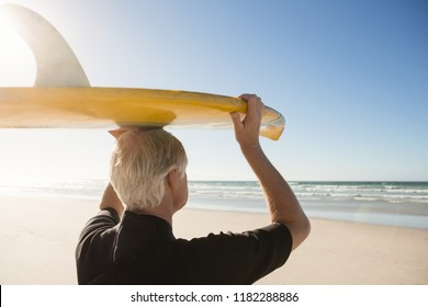 Rear view of senior man carrying surfboard on head at beach during sunny day