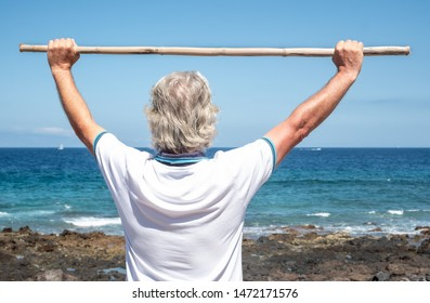 Rear view of senior man doing back exercises with the help of a cane. Blue sky and sea behind him. Healthy lifestyle. Vacations or retirement. Serenity and relax