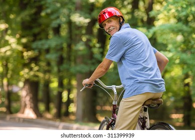 Rear view of senior man in helmet is riding bicycle in park and looking over shoulder.