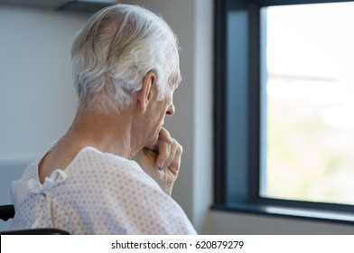 Rear view of a senior man sitting on wheelchair looking outside the window. Old man in hospital room sitting near window and thinking. Elderly patient feeling sad and alone at hospital.