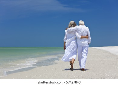 Rear view of a senior man and woman couple walking arms around each other on a deserted tropical beach with bright clear blue sky