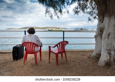 Rear view of senior woman sitting on chair admiring seascape