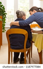 Rear view of a senior woman sitting at home beeing embraced by her granddaughter who is helping her during the day, eldercare by family members