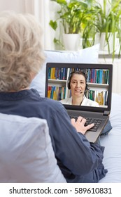 Rear view of a senior woman sitting with laptop on the sofa of her living room, having an online therapy session via the internet, psychological helpline