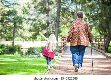Rear view of senior woman walking with little girl in park. Grandmother walking with cane holding granddaughter with hand