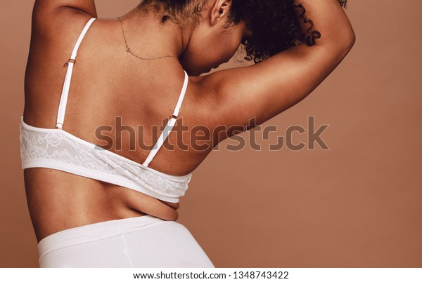 Rear view of sensual african woman posing in lingerie. Female wearing underwear on brown background.