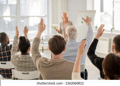 Rear view of several clever students raising their hands at lesson to answer question of their teacher