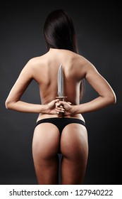 Rear view of sexy Arab woman in underwear holding a large knife behind her back.