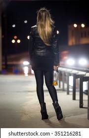 Rear view of sexy woman posing at highway at night
