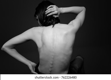 Rear View Of Shirtless Woman Against Black Background