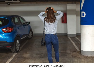Rear View Of A Shocked Woman Standing In Parking Lot After her Car Was Stolen. Car missing. Woman returned after shopping and didn't find her car on underground parking