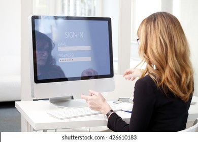 Rear view shoot of businesswoman sitting at her computer while log in and typing password to checking her bank account.
