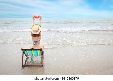 rear view shot of asian woman short hair in a blue bikini and beautiful hat, she sitting on deck chair and raising watermelon on sandy beach with happy and beauty face on summer holiday vacation