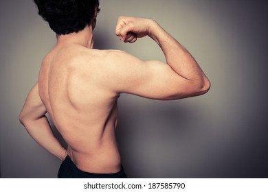 Rear view shot of athletic young man flexing his muscles