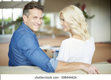 Rear view shot of a beautiful middle aged couple sitting on sofa at home and relaxing. Handsome man looking back while hugging her attractive wife.