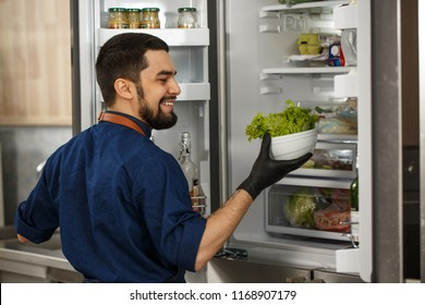 Rear view shot of a handsome bearded cheerful male professional chef smiling happily holding lettuce standing in front of an open fridge collecting ingredients for cooking salad.