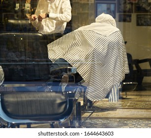 Rear view shot of handsome hairdresser cutting hair of male client. Hairstylist serving client at barber shop