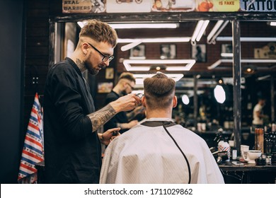 Rear view shot of handsome hairdresser cutting hair of male client. Hairstylist serving client at barber shop. Hipster young good looking man visiting hairstylist in barber shop.