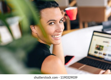Rear view shot of a happy business woman smiling and working with laptop in a cafe. Portrait of succesful young female reading news on laptop computer and drinking coffee in a resturant in the morning