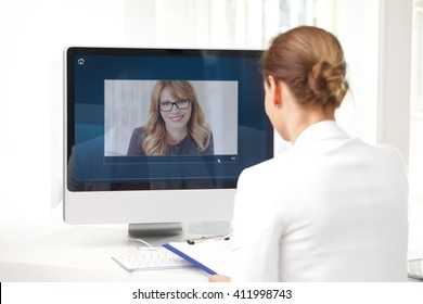 Rear view shot of middle age businesswoman sitting at her workplace and having video chat with executive professional woman.