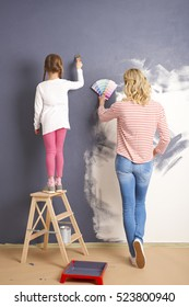 Rear view shot of a mother and daughter matching colors and painting the wall at home.
