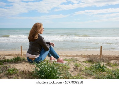 Rear view shot of relaxed middle aged woman sitting on beach and looking away.