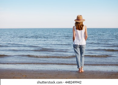 Rear view shot of a relaxed woman walking along a sandy beach while wearing straw hat and sunglasses.