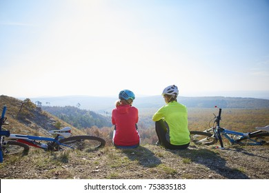 Rear view shot of a two female cyclist woman relaxing on mountain and enjoying scenery from top of the hill.
