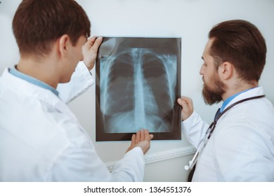 Rear view shot of a two male doctors examining x-ray scan of a patient. Medical team discussing lungs x-ray of a patient. Experienced therapists working at the clinic. Medical service concept