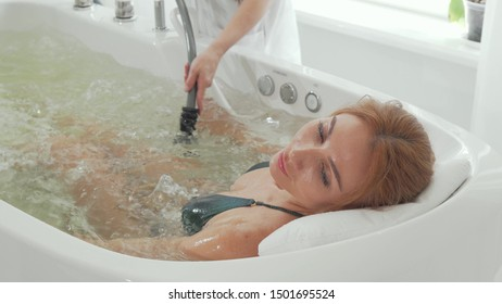 Rear view shot of a woman enjoying hydromassage in whirl pool bath. Relaxed woman getting hydromassage from professional beautician at spa center