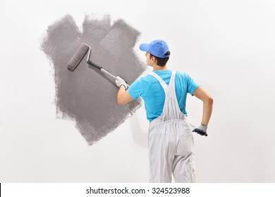 Rear view shot of a young male decorator in white overalls painting a wall with gray color