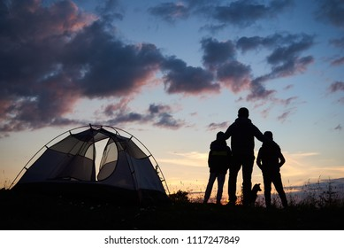 Rear view of silhouette of a father backpacker hugging two children. Tourists guys and dog stands beside camping on the top of mountain near tent at sunset under evening sky with clouds.