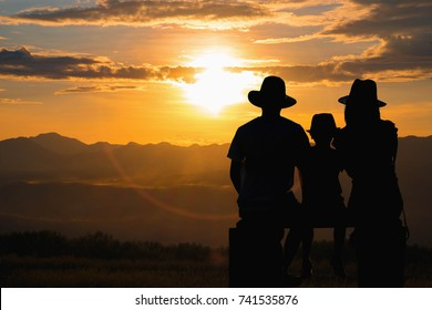 Rear view of a silhouette of three family sitting watching the sunset behind a mountain