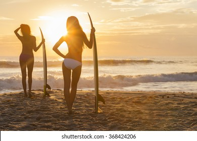 Rear view silhouette of two beautiful sexy young women surfer girls in bikini with surfboards on a beach at sunset or sunrise